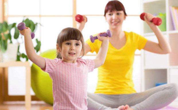 Ребенок выполняет упражнения с гантелями
